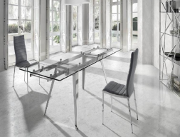 Extendable dining table with stainless steel legs and glass top. Mod. LOTUS